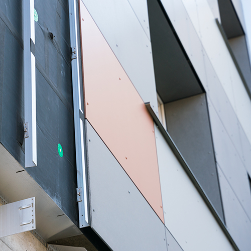Cladding boards being installed on a building facade